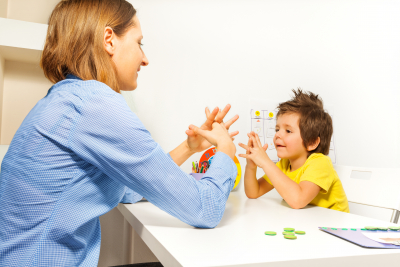 little boy exercises by putting hands and fingers together with therapist