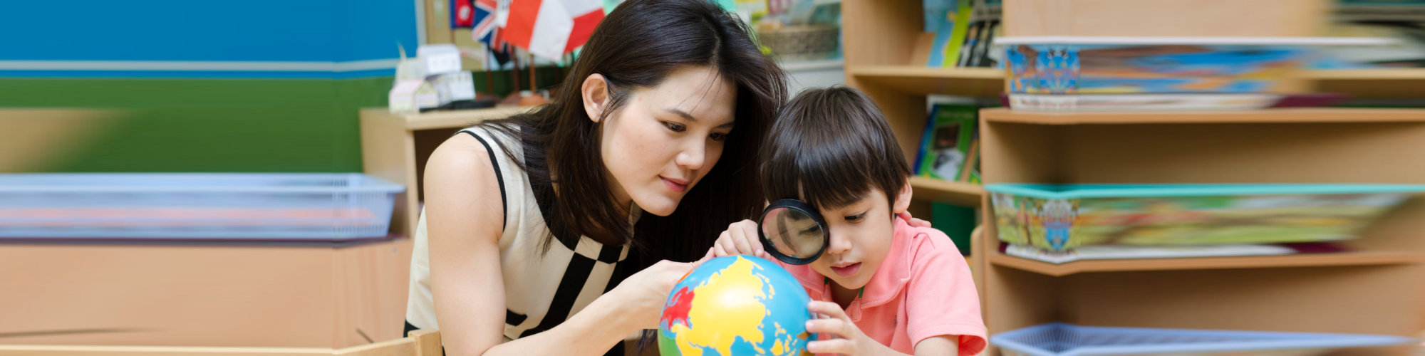 teacher and her student looking at the globe