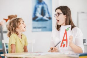 Speech therapist working with a child on a correct pronunciation using a prop
